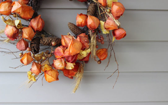 decorating a house for fall with a wreath hanging on vinyl siding